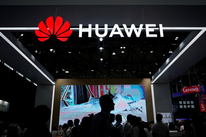 People walk past a sign board of Huawei at CES (Consumer Electronics Show) Asia 2018 in Shanghai