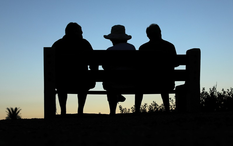 Elderly people sit on a park bench after sun set in Encinitas