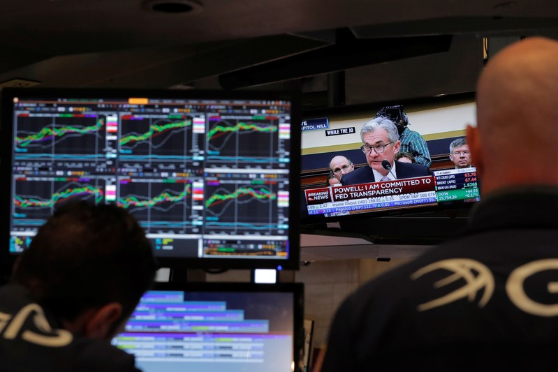 Federal Reserve Chairman Jerome Powell speaks on a television as traders work on the floor of the New York Stock Exchange in New York