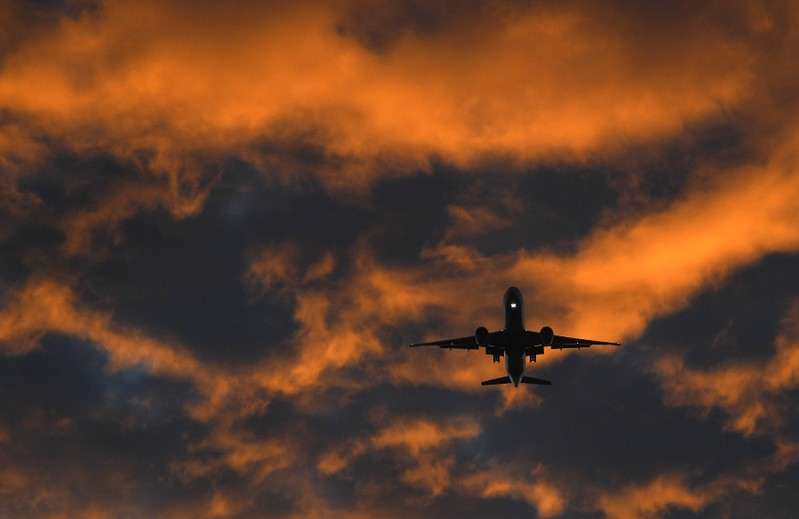 A passenger plane flies towards Heathrow airport at dawn in London, Britain