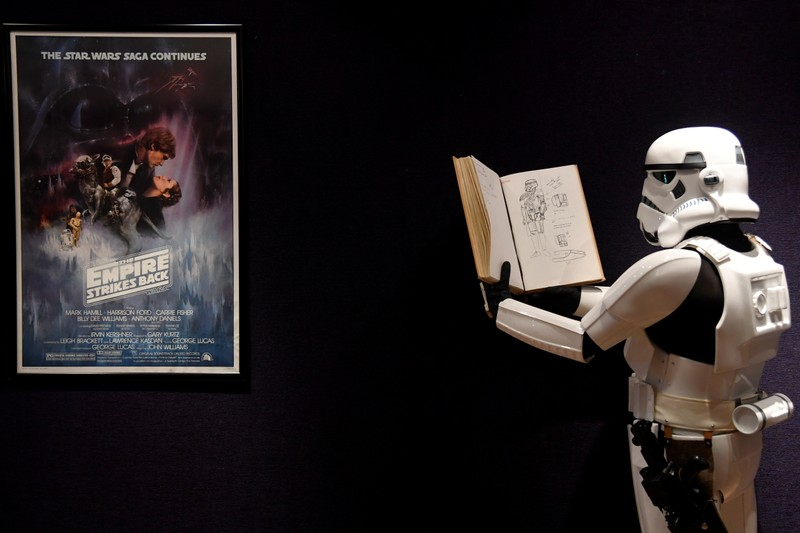 A man wearing a storm trooper costume stands in front of a Star Wars poster belonging to costume designer John Mollo, during a photo-call ahead of an auction at Bonhams in central London
