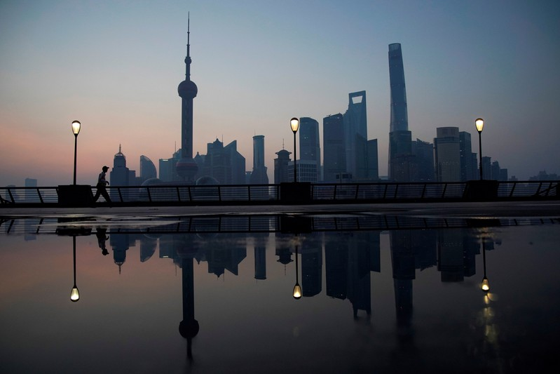 FILE PHOTO - A security guard walks on the bund in front of the financial district of Pudong in Shanghai