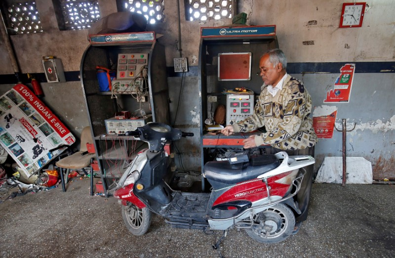 A worker checks the power supply to recharge an electric scooter inside a workshop in Ahmedabad