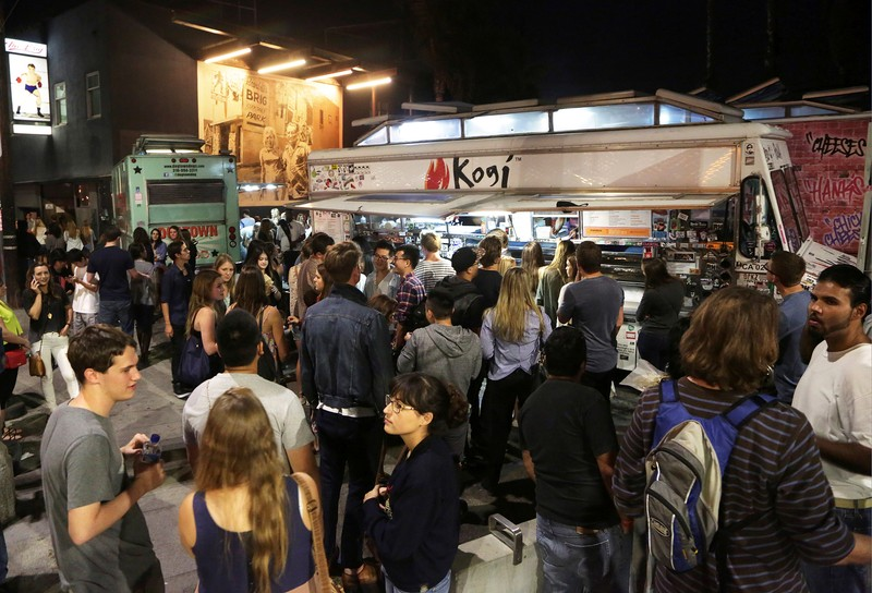 FILE PHOTO: People stand in line to order from food trucks during monthly first Friday event on Abbot Kinney Boulevard in Venice, California