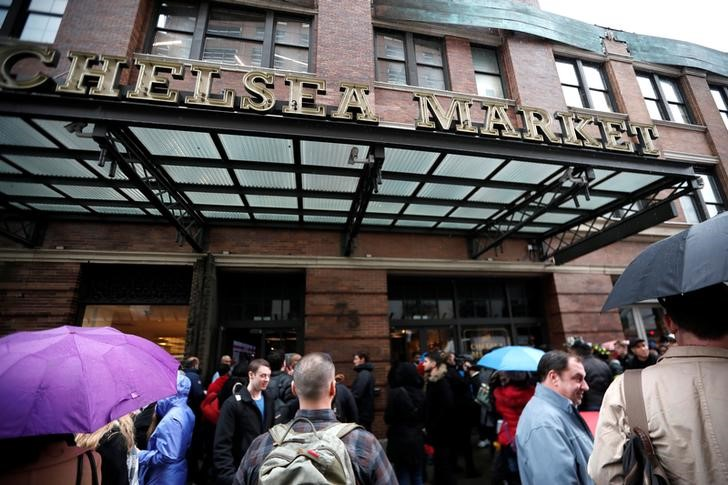 People stand outside the Chelsea Market after it was evacuated due to a rooftop fire in New York City