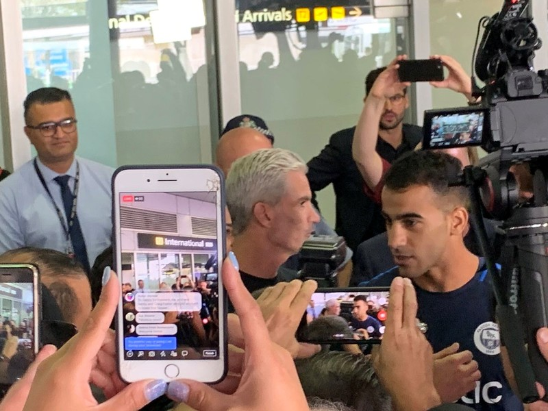 Hakeem al-Araibi, a refugee Bahraini footballer who was released from a Thai prison, is seen with Craig Foster as he arrives at the airport in Melbourne