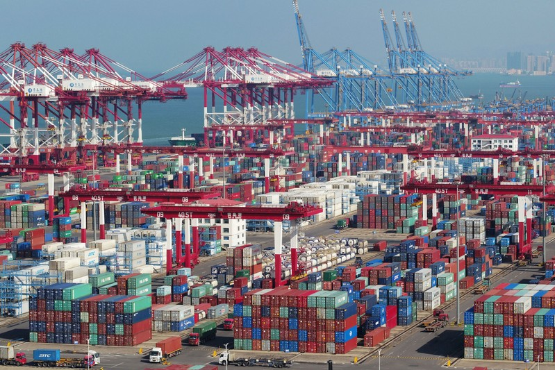 Containers and trucks are seen at a terminal of the Qingdao port in Shandong