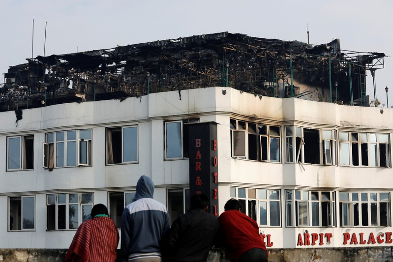 Onlookers stand on the rooftop of a building as they look at a hotel where a fire broke out in New Delhi