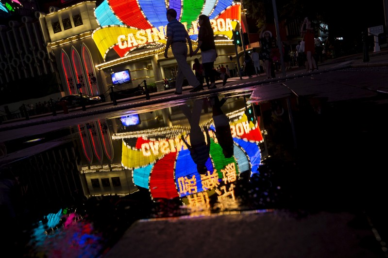 FILE PHOTO: Mainland Chinese visitors walk in front of Casino Lisboa, owned by SJM Holdings, in Macau, China