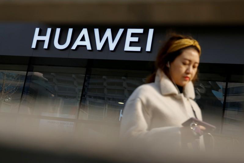 FILE PHOTO: A woman walks past a Huawei shop in Beijing