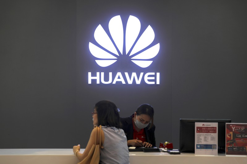 A woman sits next to a salesperson at a Huawei shop in Bangkok, Thailand
