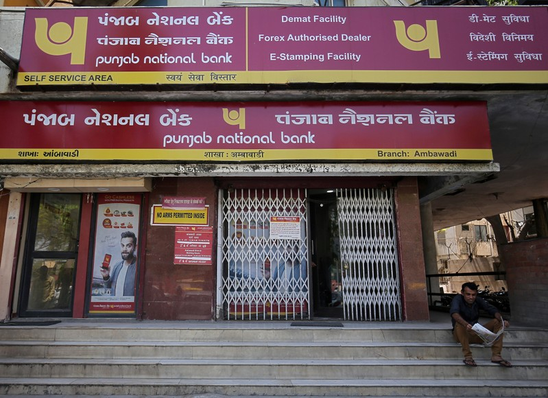 FILE PHOTO: A man reads a newspaper outside a branch of Punjab National Bank in Ahmedabad