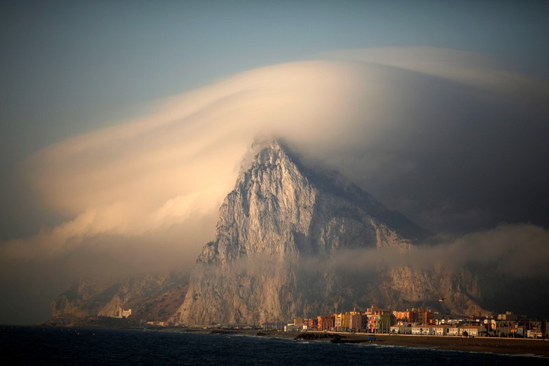 FILE PHOTO: Cloud partially covers Rock of the British territory of Gibraltar at sunrise before Spanish fishermen take part in a protest in Algeciras bay