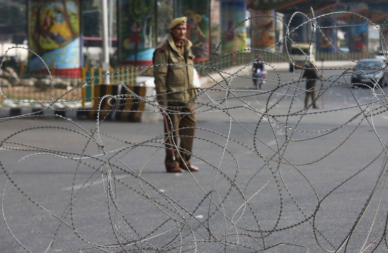 A policeman stands guard at a street during a curfew in Jammu