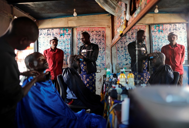 Yaya Niass, a hairdresser who works out of a road-side shack, is pictured inside his shop in Pikine, on the outskirts of Dakar
