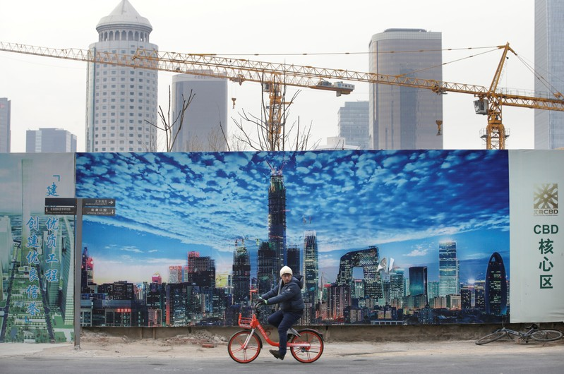 A man cycles outside the construction sites in Beijing's central business area