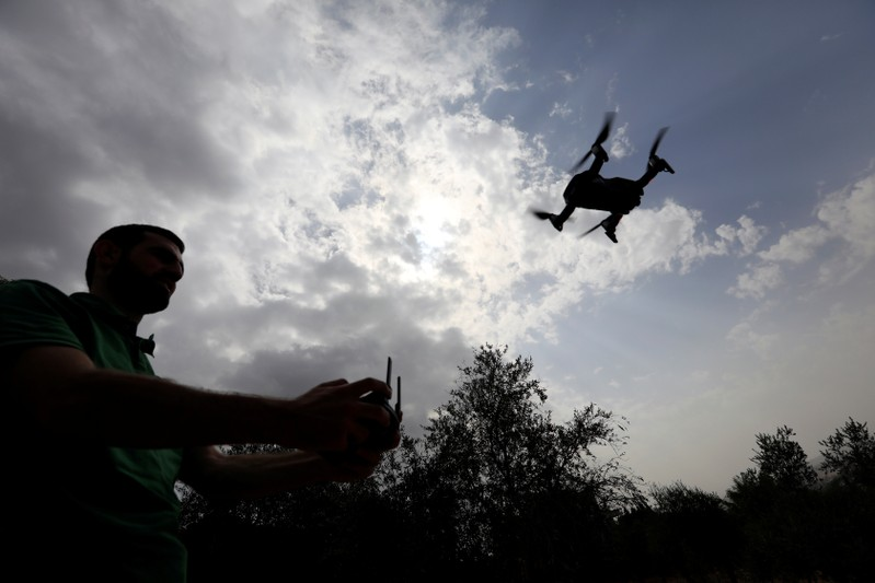 A man operates a drone over olive trees in Nabatieh