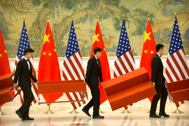 Aides set up platforms before a group photo with members of U.S. and Chinese trade negotiation delegations at the Diaoyutai State Guesthouse in Beijing