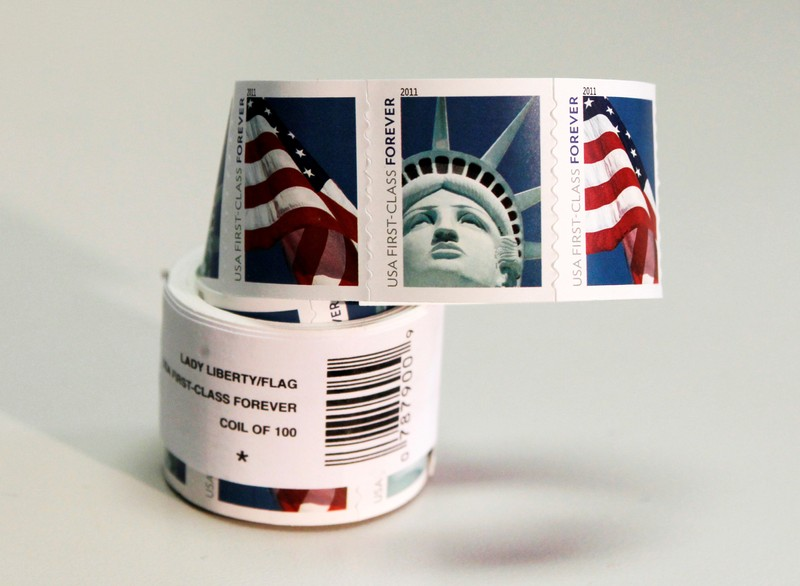 FILE PHOTO: A coil of 100 new USA First Class postage stamps, bearing an image of the Statue of Liberty and U.S. flags, is shown in Washington