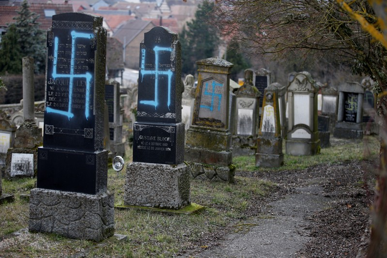 Graves desecrated with swastikas are seen in the Jewish cemetery in Quatzenheim