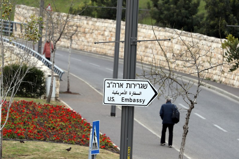 A man walks next to a road sign directing to the U.S. embassy in Jerusalem
