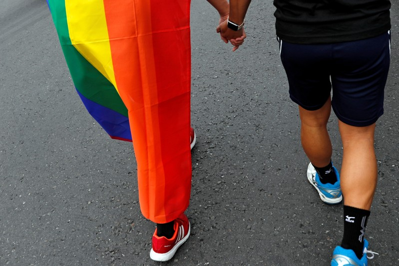FILE PHOTO: Same-sex marriage supporters hold hands as they taking part in a LGBT pride parade after losing in the marriage equality referendum, in Kaohsiung