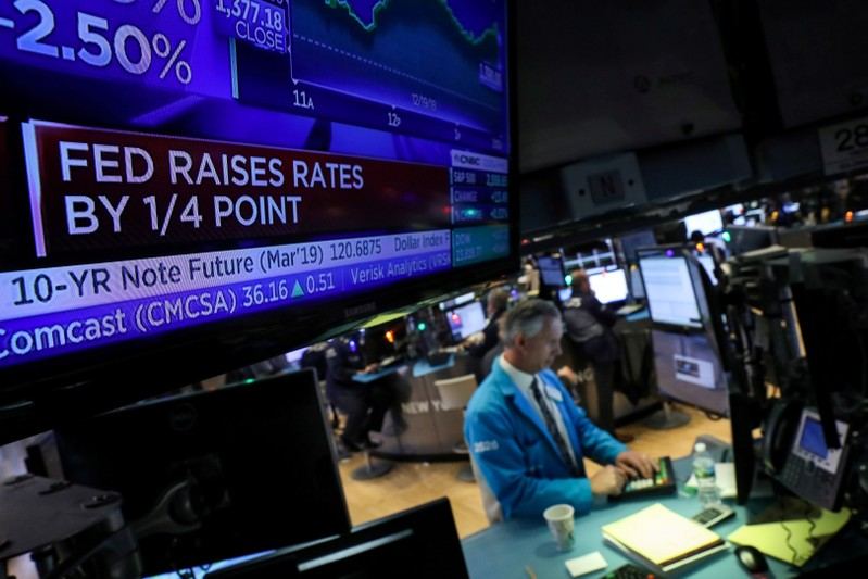 FILE PHOTO: A screen displays the headlines that the U.S. Federal Reserve raised interest rates as a trader works at a post on the floor of the NYSE in New York