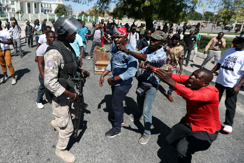 Local residents argue with a policeman while the casket of a man shot dead during anti-government protests lies on the ground in Port-au-Prince