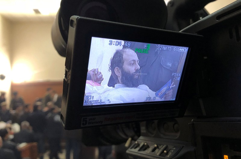 Ramon Rasmi Mansour, known as Faltaous al-Makari, is seen on screen of video camera in a courtroom in Damanhour