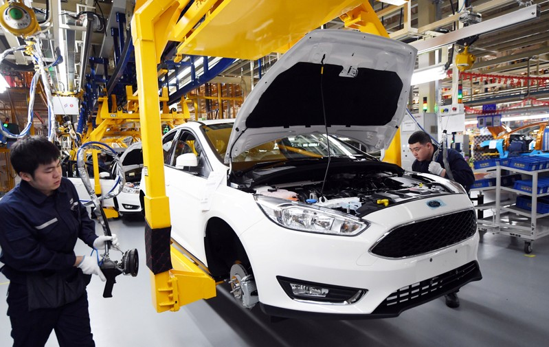 Workers assemble vehicles at a plant of Changan Ford in Harbin