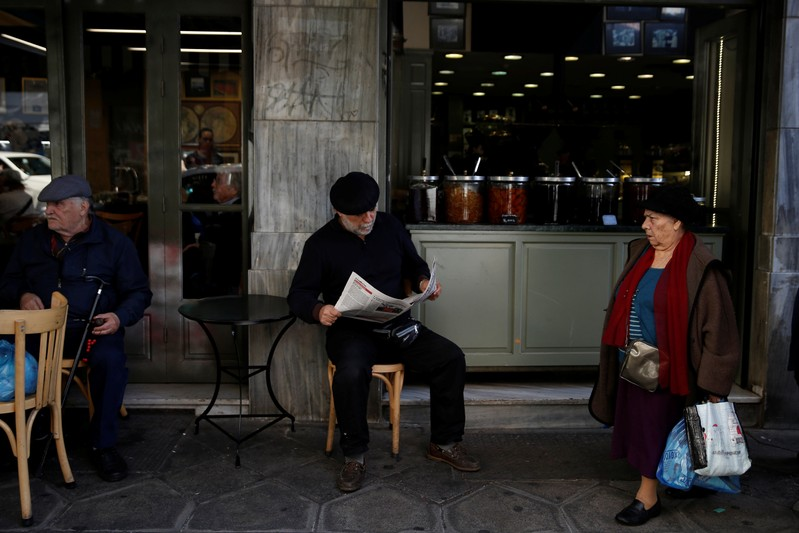 A man reads a newspaper at a coffee shop in central Athens