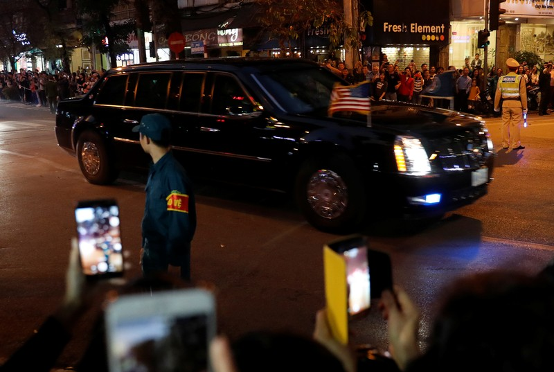 The motorcade of U.S. President Donald Trump passes bystanders on a road near the Metropole Hotel in Hanoi
