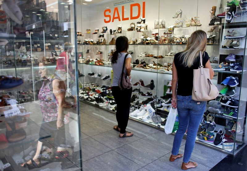 Women stand in a shoes shop in Rome