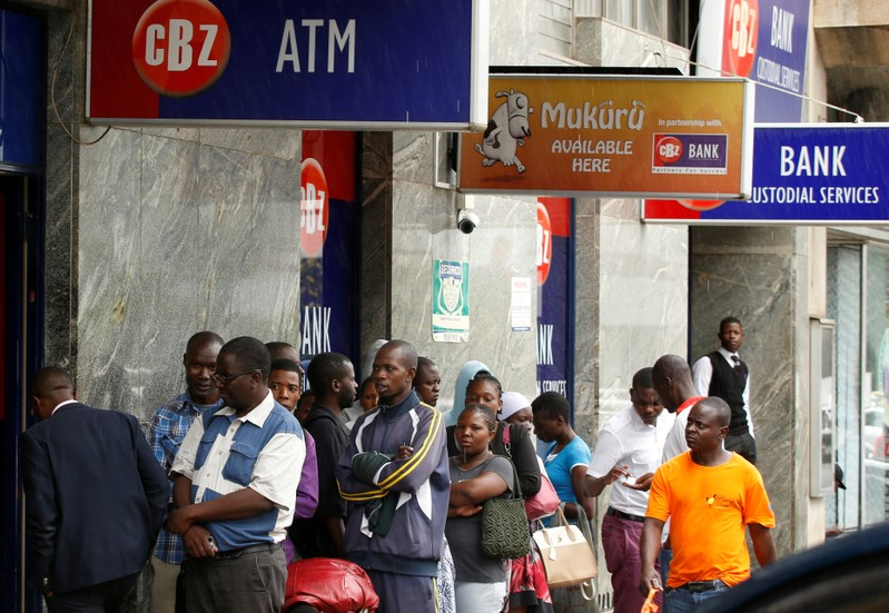 FILE PHOTO: Zimbabweans queue outside a bank in Harare