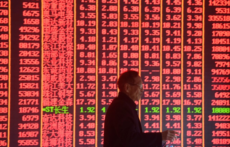 FILE PHOTO: Man is seen in front of an electronic board showing stock information on the first day of trading in the Year of the Pig at a brokerage house in Hangzhou