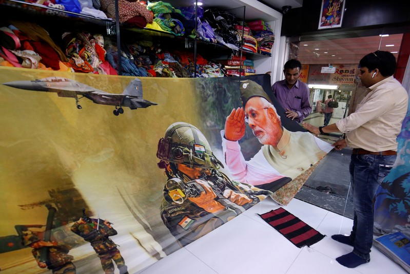 Traders display a sari with printed images of India's Prime Minister and Indian Army inside their shop in Surat
