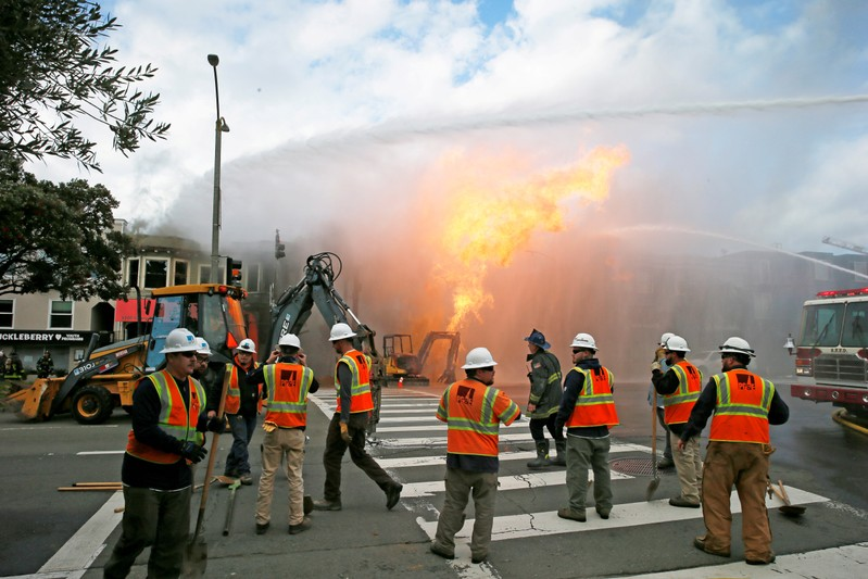 PG&E officials are seen as firefighters battle a fire following an explosion at Geary boulevard and Parker Avenue in San Francisco