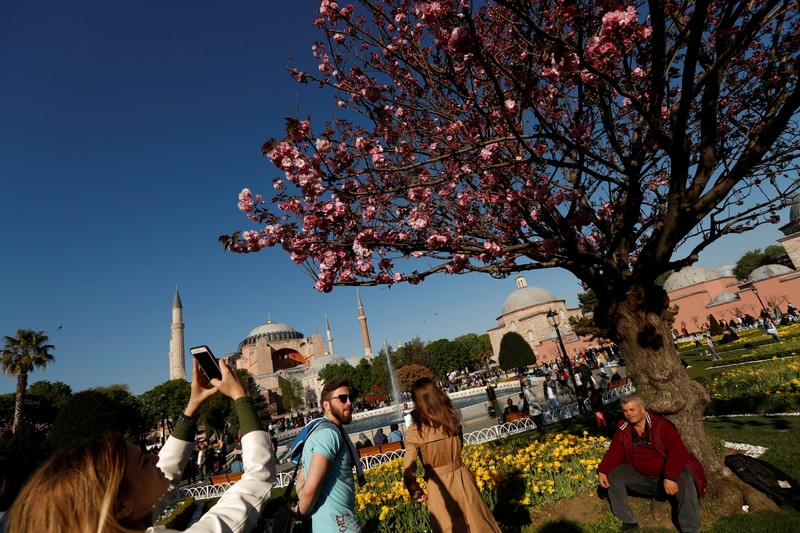 A foreign tourist, with the Byzantine-era monument of Hagia Sophia in the background, take pictures at Sultanahmet square in Istanbul