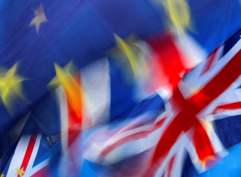 FILE PHOTO: British and EU flags flutter outside the Houses of Parliament during a pro-Brexit and anti-Brexit demonstration in London