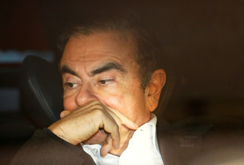 FILE PHOTO : Former Nissan Motor Chairman Carlos Ghosn sits inside a car as he leaves his lawyer's office after being released on bail from Tokyo Detention House, in Tokyo