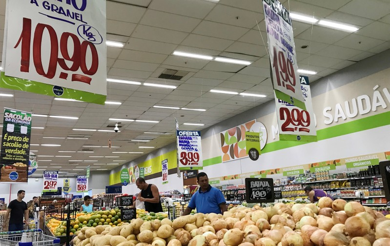FILE PHOTO: Customers look at the prices at a supermarket in Rio de Janeiro