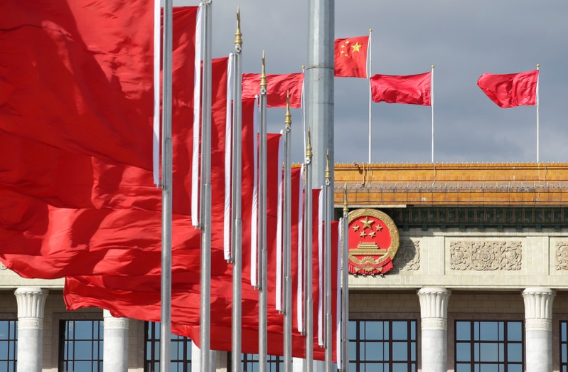 Red flags flutter in front of the Great Hall of the People in Beijing