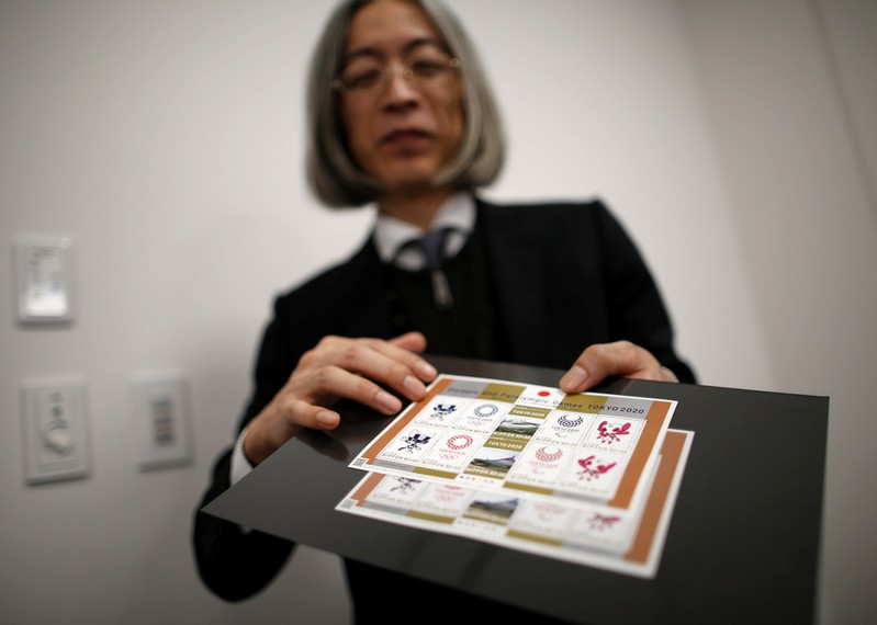 Japan Post Co. Ltd. chief stamp designer Akira Tamaki shows off the sheets of commemorative stamps for Tokyo 2020 Olympic and Paralympic Games in Tokyo