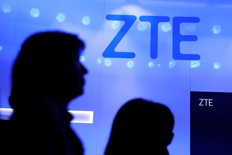 FILE PHOTO: People walk past a ZTE logo outside its booth at the Mobile World Congress in Barcelona