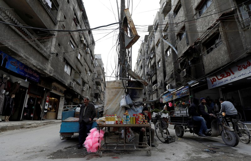 A man sells goods along a street in Ein Terma, a district of eastern Ghouta