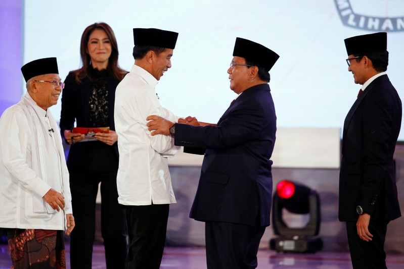 FILE PHOTO - Indonesia's presidential candidate Joko Widodo shakes hands with his opponent Prabowo Subianto as their running mates Ma'ruf Amin and Sandiaga Uno smile after a televised debate in Jakarta