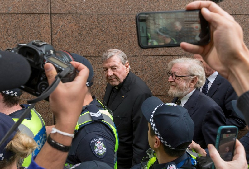FILE PHOTO - Vatican Treasurer Cardinal George Pell is surrounded by Australian police and members of the media as he leaves the Melbourne Magistrates Court in Australia