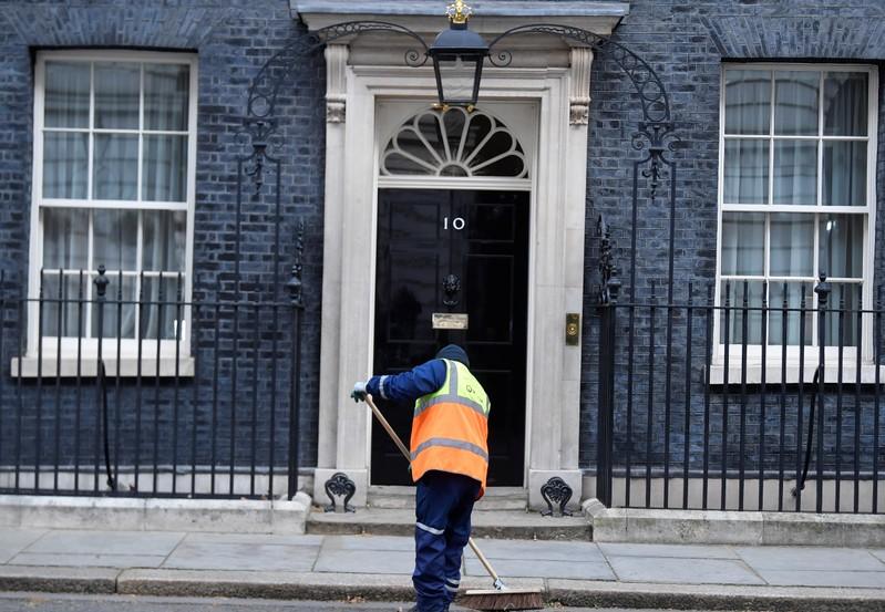 Man sweeps outside 10 Downing Street in London