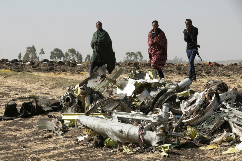 Ethiopian police officers walk past the debris of the Ethiopian Airlines Flight ET 302 plane crash, near the town of Bishoftu, near Addis Ababa