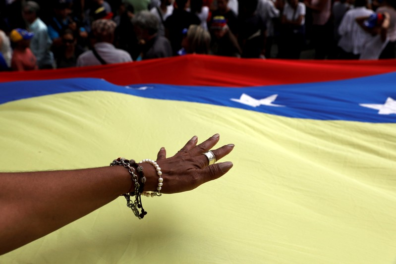 A hand is seen over the national flag during a protest against Venezuelan President Nicolas Maduro's government in Caracas